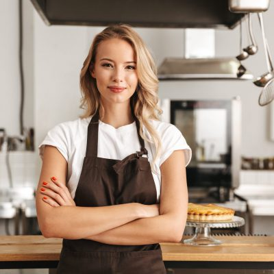 Smiling young woman chef cook in apron standing at the kitchen, looking at camera